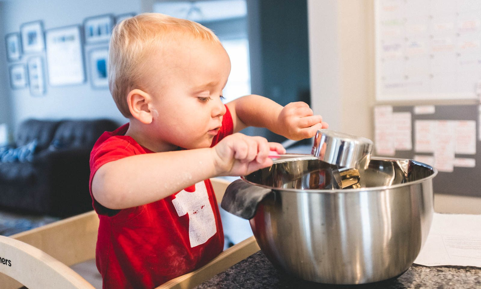 toddler cooking with food allergies using stainless steel measuring cups and mixing bowl