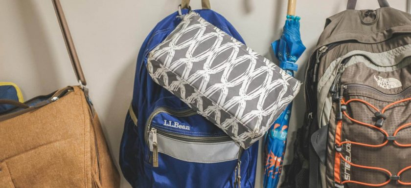 food allergy emergency kit/med bag hanging with an LL Bean backpack in an entryway