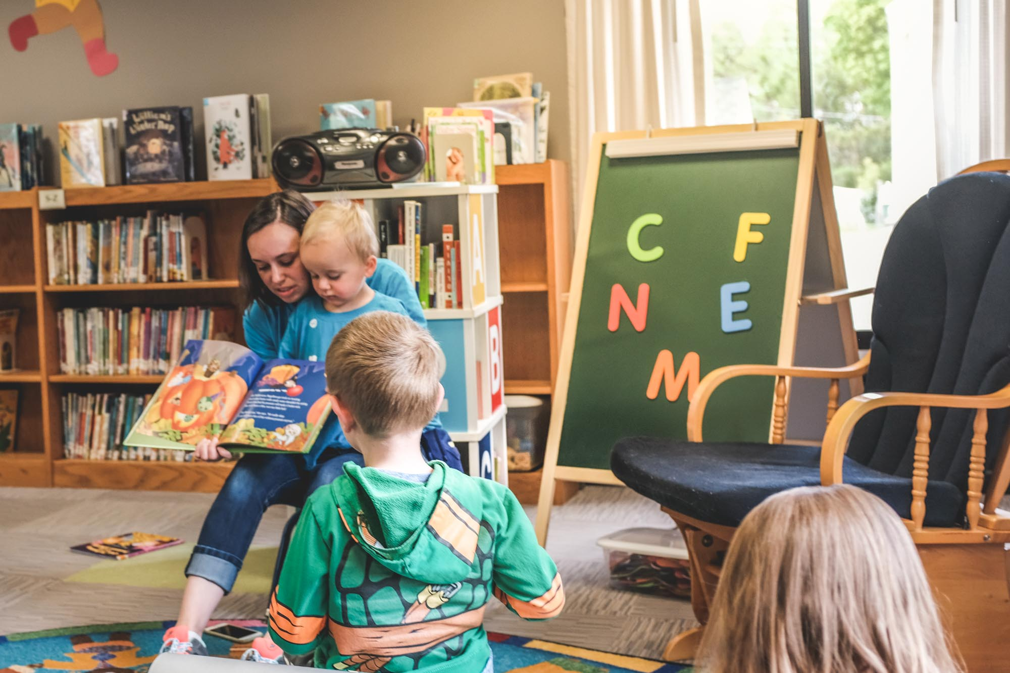 mom and toddler read bugabees during a story time for one of their food allergy awareness events