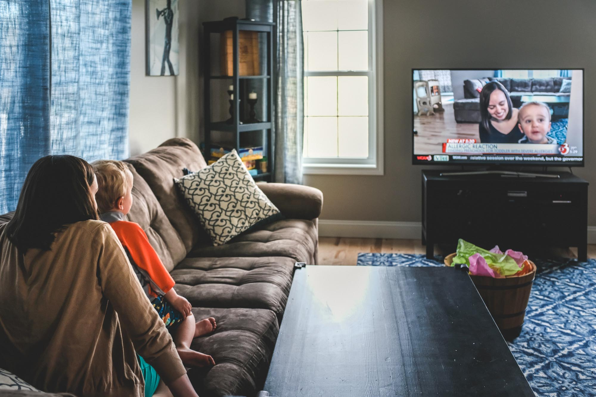 mom and toddler watch a tv segment for one of their food allergy awareness events