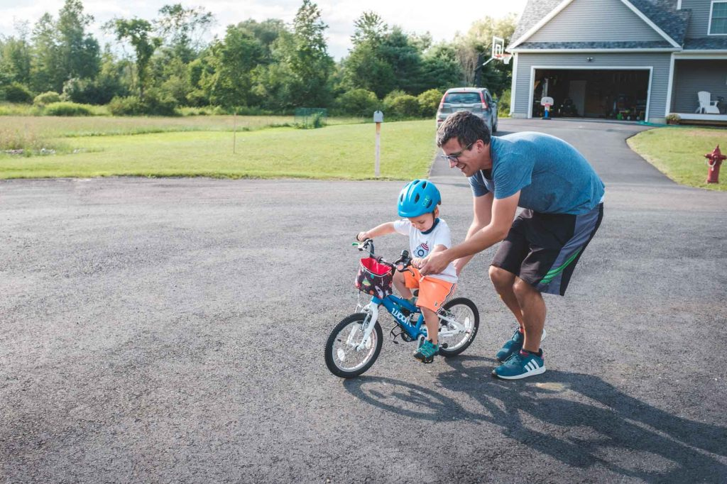 dad helping a toddler learn to bike on a woom bike