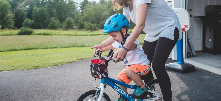 mom helping a toddler learning to bike on a woom bike