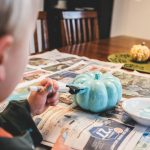 toddler paints a teal pumpkin for their eco-friendly teal pumpkin project celebration