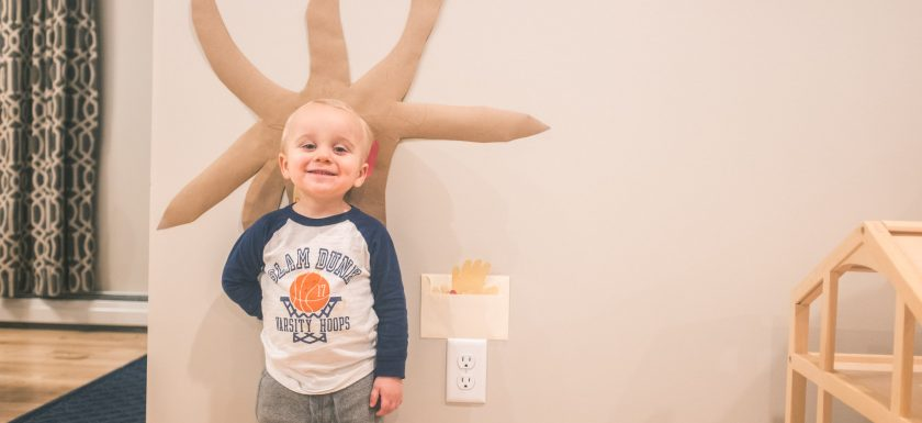 toddler standing in front of the starts of his thankful tree