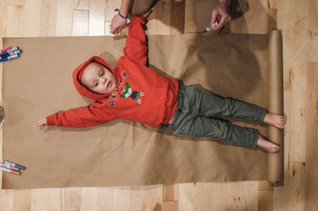 child laying down to trace his body for a thankful tree