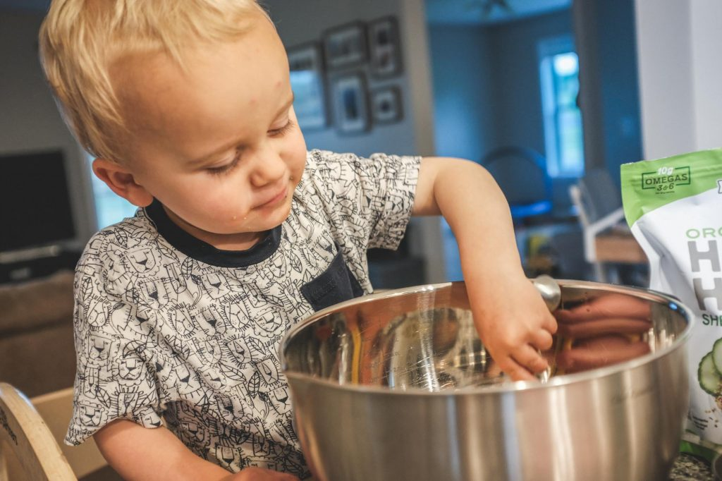 toddler scooping out allergy-friendly granola